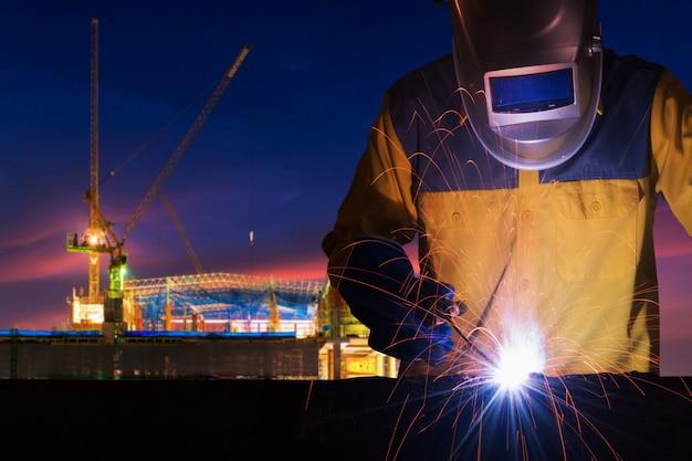 Trabalhador industrial, soldagem de estrutura de aço para projeto de construção de infra-estrutura Foto Premium