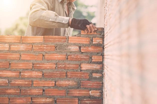 Trabalhador, instalar, parede tijolos, em, processo, de, edifício casa Foto Premium