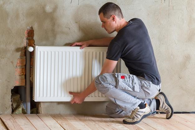 Trabalhador jovem bonito profissional encanador instalar radiador de aquecimento em uma sala vazia de um apartamento ou casa recém-construída. conceito de construção, manutenção e reparação. Foto Premium