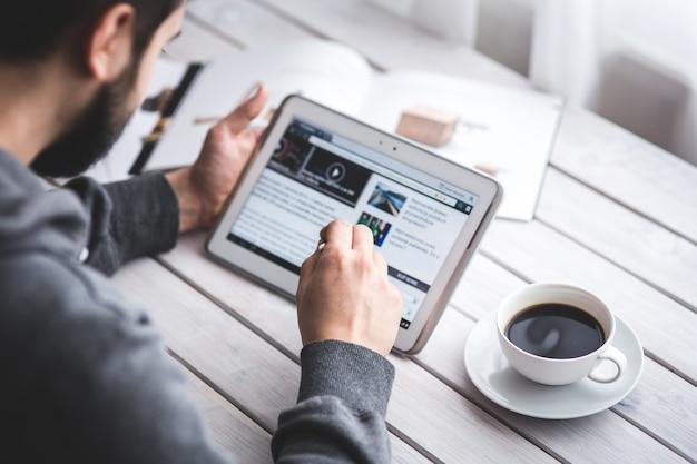 Trabalhador leitura de notícias com a tabuleta Foto gratuita