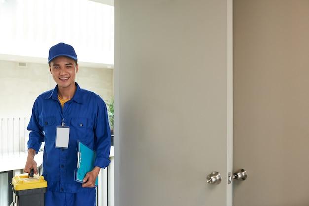 Trabalhador manual asiático alegre que chega na chamada de casa Foto gratuita