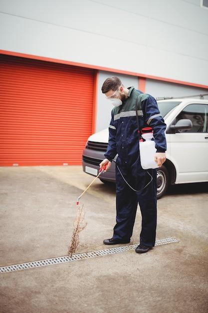 Trabalhador manual com inseticida em pé na frente de sua van Foto Premium