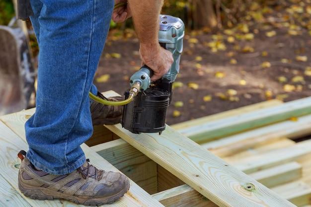 Trabalhador manual de instalação de piso de madeira no pátio, trabalhando com pistola de prego para unha Foto Premium