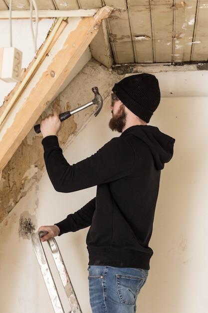 Trabalhador manual em pé em uma escada e reformando uma casa, usando ferramentas como um martelo Foto Premium