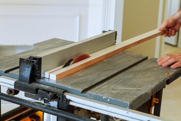Trabalhador manual irreconhecível cortador de serra circular de madeira na casa nova Foto Premium