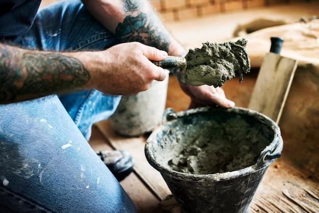 Trabalhador manual preparar cimento uso para construção Foto gratuita