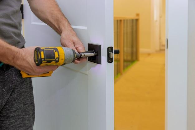 Trabalhador manual que instala a fechadura da porta na sala com chave de fenda Foto Premium
