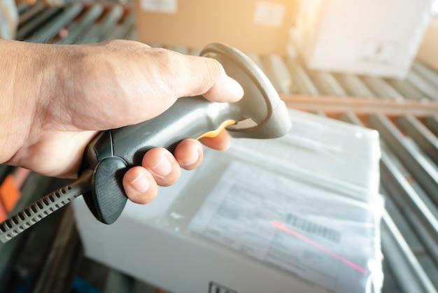 Trabalhador mão segurando o scanner de código de barras com digitalização para caixas de um pacote Foto Premium