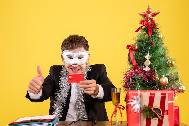 Trabalhador masculino de vista frontal usando máscara de festa e segurando um cartão do banco Foto gratuita