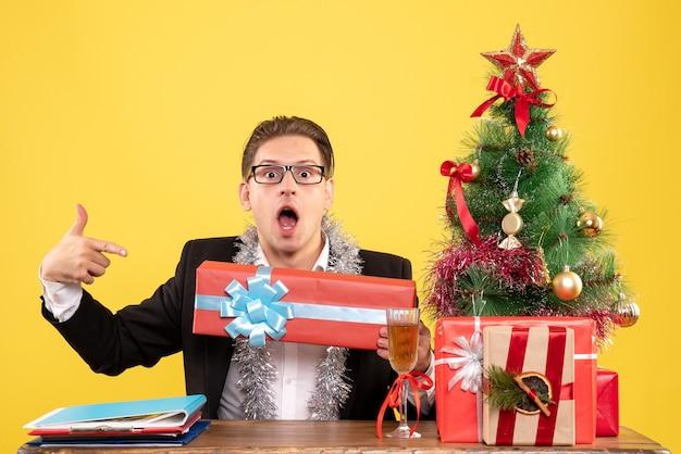 Trabalhador masculino sentado de frente e segurando um presente de natal Foto gratuita