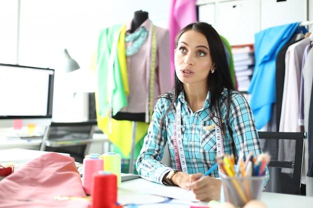 Trabalhador no ponto de serviço que recebe ordens para reparos de roupas se comunica com o cliente Foto Premium