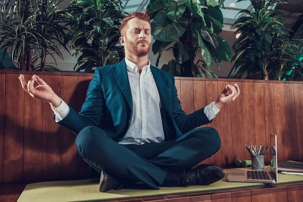 Trabalhador no terno que medita no banco no escritório. Foto Premium