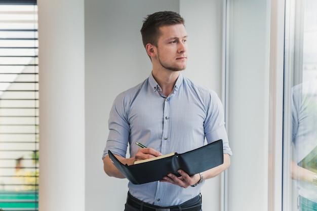 Trabalhador pensativo posando com caderno Foto gratuita