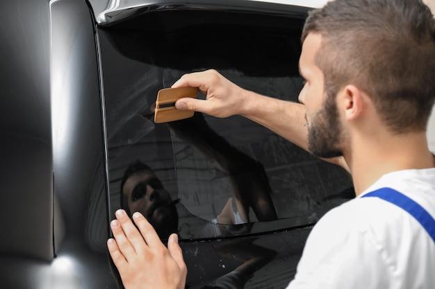 Trabalhador pintando vitrines de carros em uma loja Foto Premium