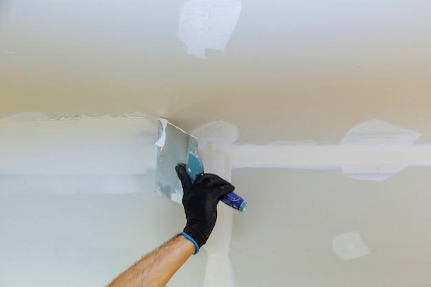 Trabalhador puttied parede usando uma espátula de tinta Foto Premium