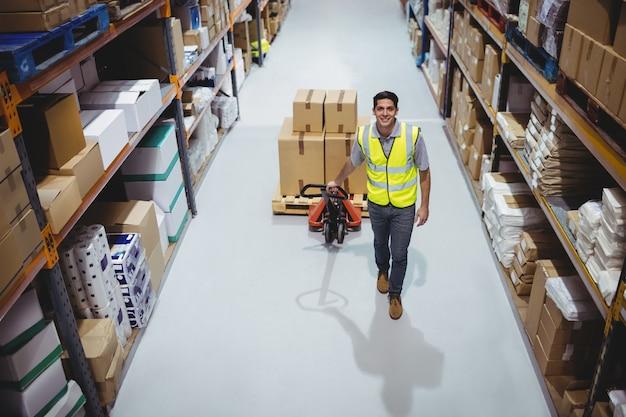 Trabalhador, puxando o carrinho com caixas no armazém Foto Premium