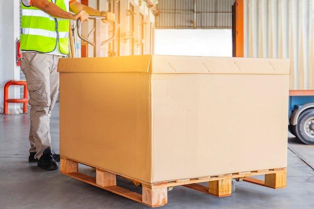 Trabalhador que descarrega carga pesada de paletes com o contêiner de caminhão Foto Premium