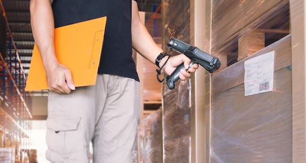 Trabalhador que escaneia o leitor de código de barras com etiqueta de mercadorias. equipamento informático para gestão de inventário em armazém. Foto Premium