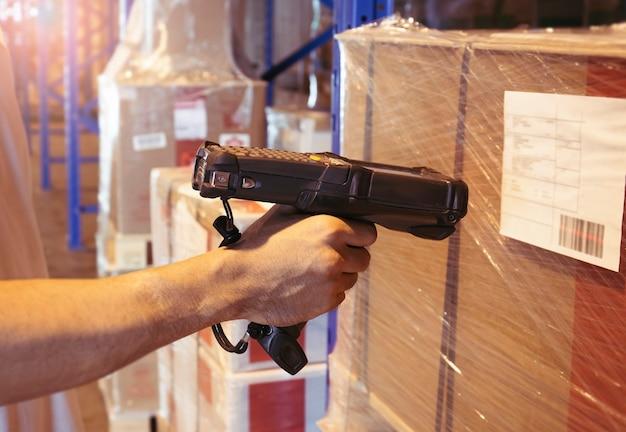 Trabalhador que faz a varredura de scanner de código de barras nos produtos no armazém. Foto Premium