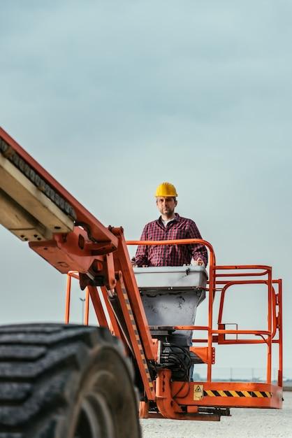 Trabalhador que opera o elevador reto da lança Foto Premium