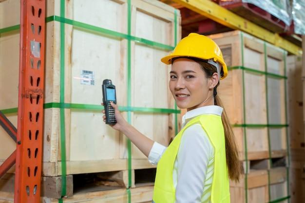Trabalhador que trabalha verificando e digitalizando produtos de pacote pelo scanner de código de barras a laser no grande armazém, logística e conceito de exportação. Foto Premium