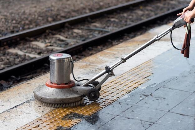 Trabalhador que usa a máquina do purificador para limpar e polir o assoalho. limpeza de manutenção de trem na estação ferroviária. Foto Premium