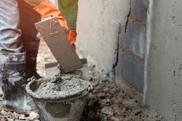 Trabalhador, reboco cimento na parede para construção de casa Foto Premium