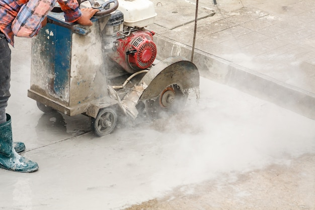 Trabalhador usando máquina de lâmina de serra de diamante cortando estrada de concreto no canteiro de obras Foto Premium