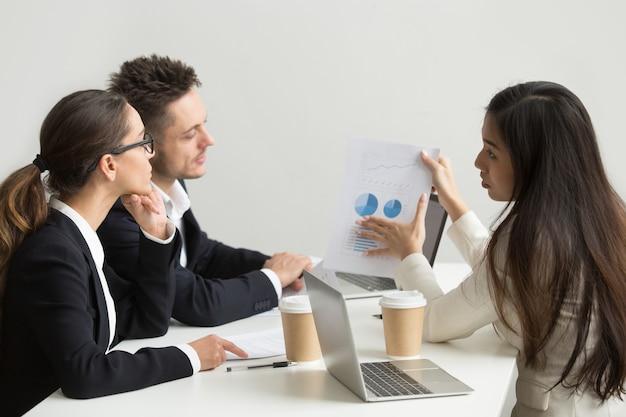 Trabalhadora, apresentando modelos visuais para colegas de trabalho Foto gratuita