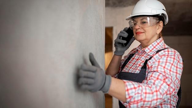 Trabalhadora da construção civil com capacete e smartphone Foto gratuita