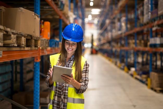 Trabalhadora de armazém verificando inventário em tablet digital em grande área de armazenamento de armazém de distribuição Foto gratuita