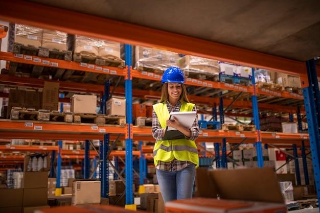 Trabalhadora de armazém verificando inventário no armazém de distribuição Foto gratuita
