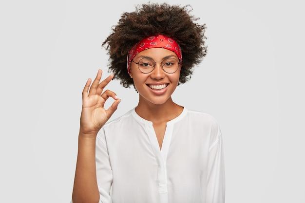 Trabalhadora étnica satisfeita faz um gesto de aprovação, tem o trabalho sob controle Foto gratuita