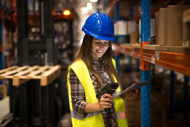 Trabalhadora sorridente segurando tablet e leitor de código de barras, verificando o estoque no armazém de distribuição Foto gratuita