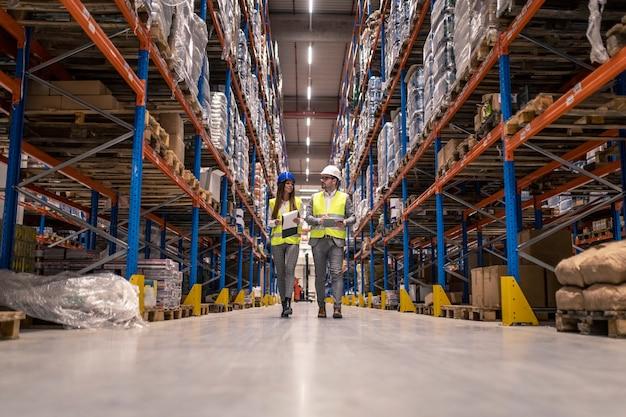 Trabalhadores com capacetes e jaquetas reflexivas caminhando pelo grande corredor do armazém verificando as condições das mercadorias Foto gratuita