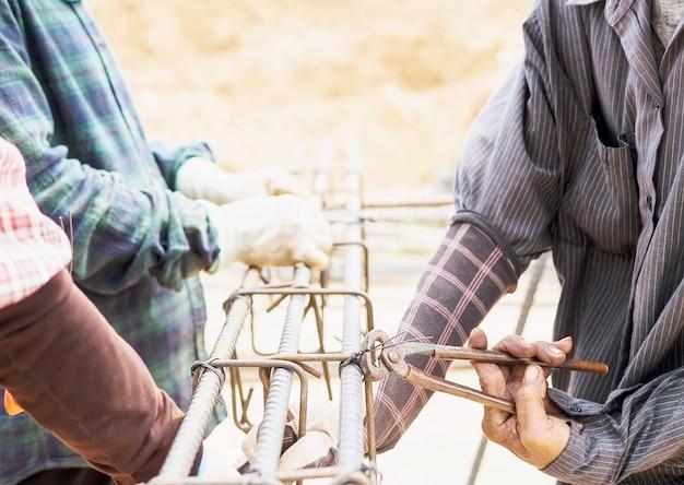 Trabalhadores da construção civil estão instalando hastes de aço em coluna de concreto armado Foto gratuita
