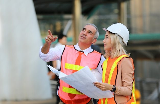 Trabalhadores da construção civil olhando plantas no canteiro de obras Foto Premium