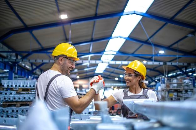 Trabalhadores da fábrica se cumprimentando na linha de produção Foto gratuita