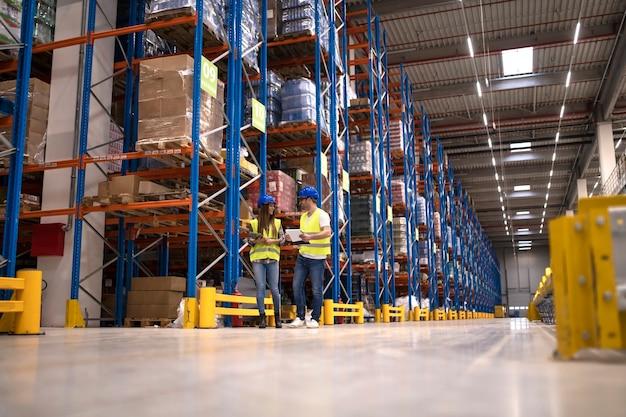 Trabalhadores de armazém discutindo sobre logística e pacotes de distribuição para o mercado Foto gratuita