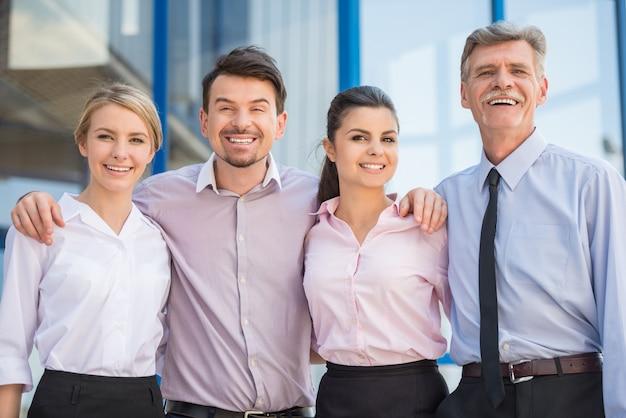Trabalhadores de escritório em pé na frente do escritório juntos. Foto Premium