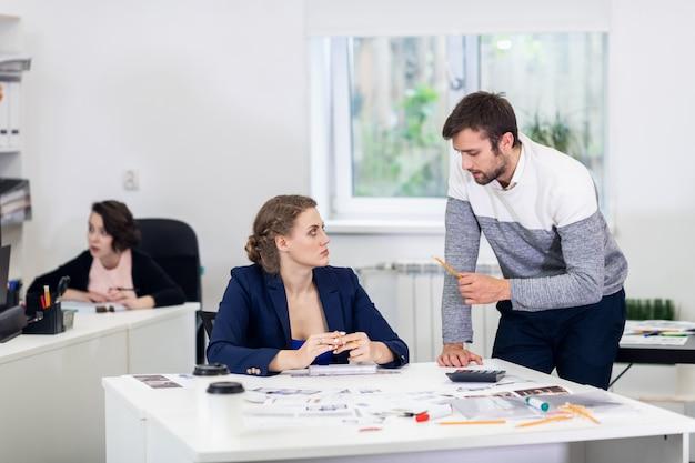 Trabalhadores de escritório em um espaço aberto, fazendo coisas diferentes, colegas conversando, discutindo projetos, trabalhando em pcs, fazendo alguma papelada. conceito de coworking Foto Premium