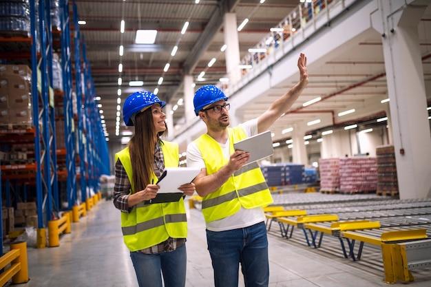 Trabalhadores do armazém consultando uns aos outros na grande área de armazenamento da fábrica Foto gratuita