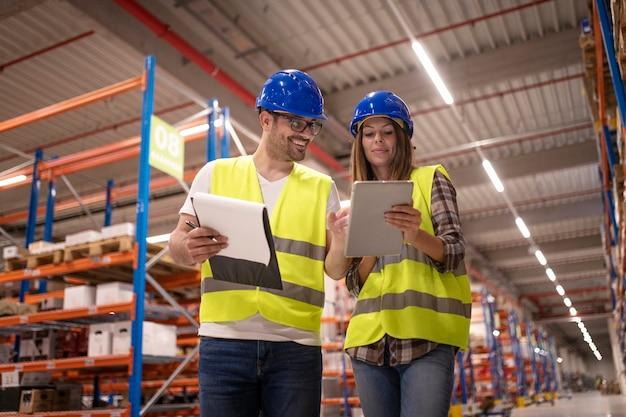 Trabalhadores do armazém controlando a distribuição no tablet em uma grande área de armazenamento do armazém Foto gratuita