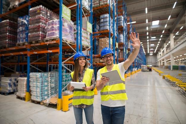 Trabalhadores do armazém verificando a organização e distribuição de produtos em grande área de armazenamento Foto gratuita