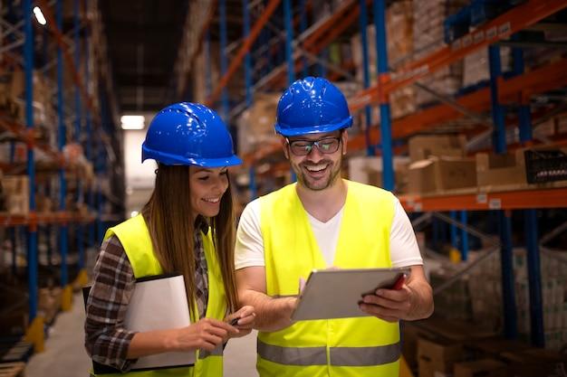 Trabalhadores do armazém verificando o status da remessa no computador tablet Foto gratuita