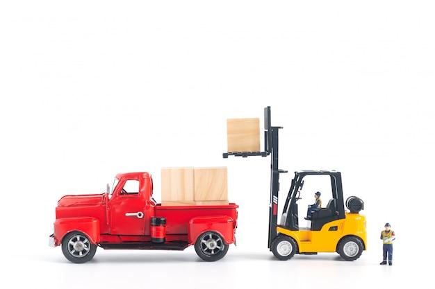 Trabalhadores em miniatura, carregando carga na retirada Foto Premium