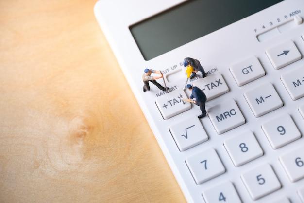 Trabalhadores em miniatura, cavando o botão de imposto na calculadora Foto Premium