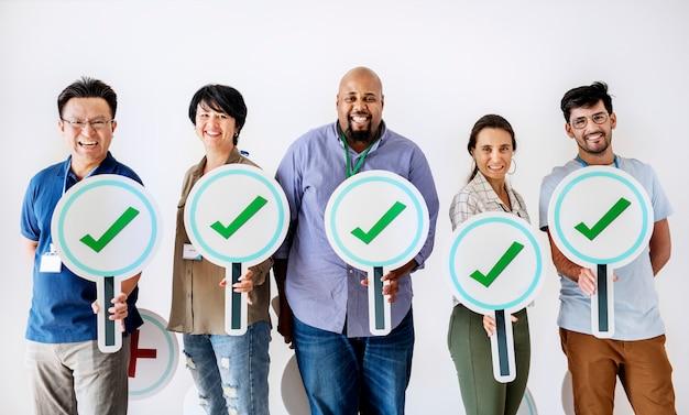 Trabalhadores em pé e segurando os logotipos de carrapatos corretos Foto Premium