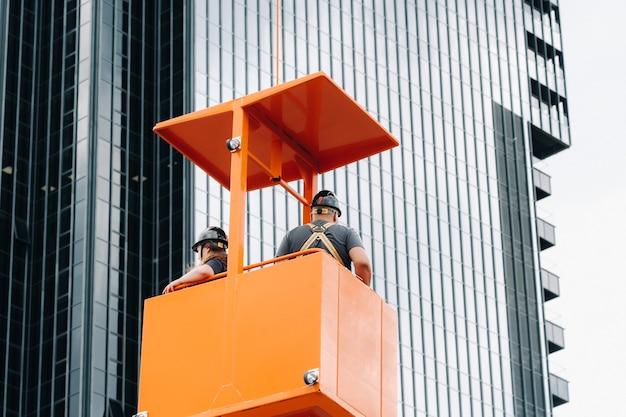 Trabalhadores em um berço de construção sobem em um guindaste até um grande edifício de vidro. o guindaste levanta os trabalhadores no assento do carro. construção. Foto Premium