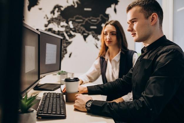 Trabalhadores em uma empresa de ti trabalhando em um computador Foto gratuita
